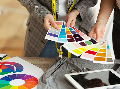 Close up of female fashion stylist and customer holding color samples choosing design for new dress, copy space